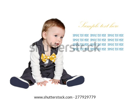 adorable baby wearing classic vest and colorful bowtie looking at sample text on white background - stock photo
