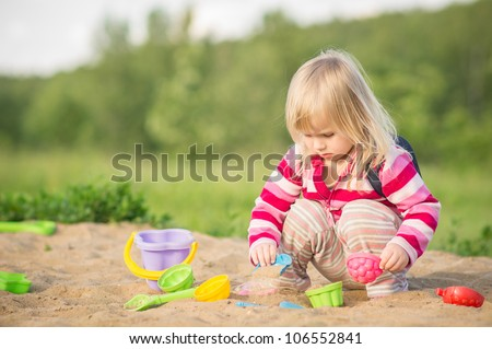 Adorable baby with bag play with toys on sandbox - stock photo