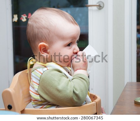 Adorable baby with bib and mouth stained with blueberry jam trying to clean himself with a handkerchief - stock photo