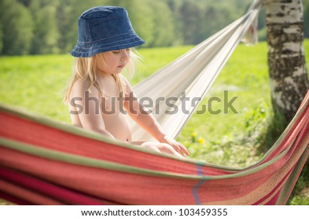 Adorable baby with blue hat sit in hammock - stock photo