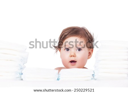 Adorable baby with bunch of diapers - stock photo