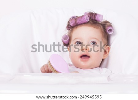 Adorable baby with hair curlers and comb - stock photo