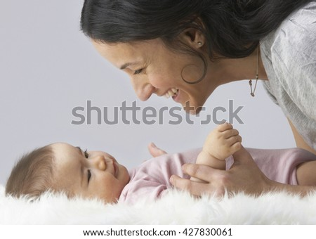 Adorable baby with his mother in studio shot
