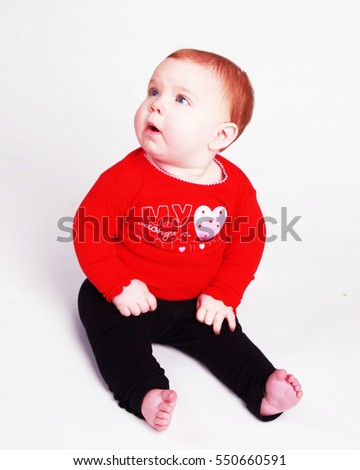 Adorable baby with red hair looking up and to her right with a quizzical look on her face.