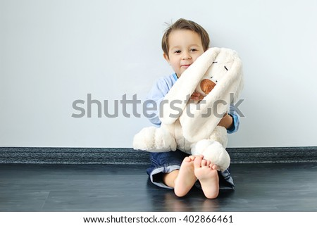 Adorable baby with teddy rabbit  on cozy floor in the room, close up. - stock photo