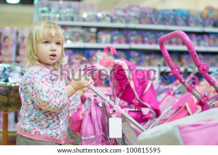 Adorable baby with toy carriage in mall
