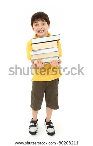 Adorable back to school boy child with stack of text books in arms walking over white background.
