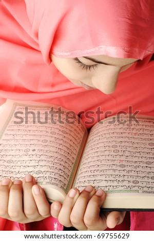 Adorable beautiful girl reading Koran - stock photo