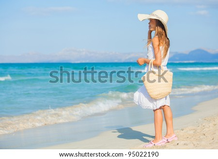 Adorable beautiful girl wearing elegant hat having fun on the tropical beach