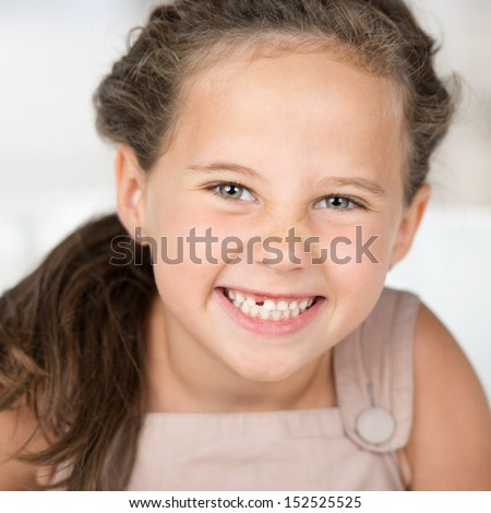 Adorable beautiful little girl grinning at the camera showing off her missing front tooth, close up portrait - stock photo