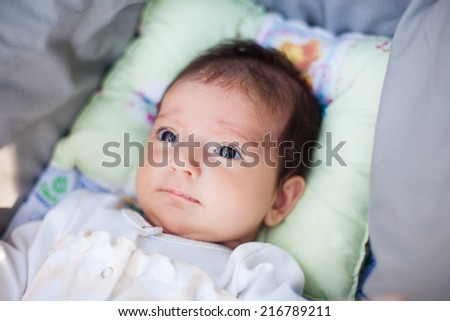 Adorable beautiful newborn baby looking up with a look of wonderment