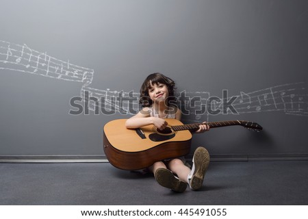 Adorable beauty plays the guitar with the light smile on her face. Big acoustic musical instrument in childish small hands. Painted with chalk stave on the neutral background. - stock photo