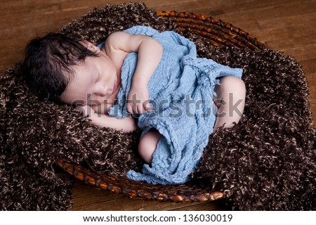 Adorable biracial baby fast asleep in a basket and wrapped in a blue cheesecloth. - stock photo