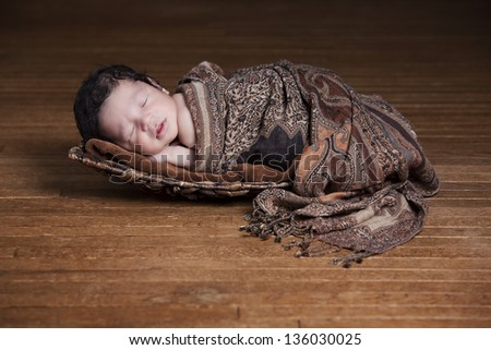 Adorable biracial baby fast asleep in a basket and wrapped in a scarf. - stock photo