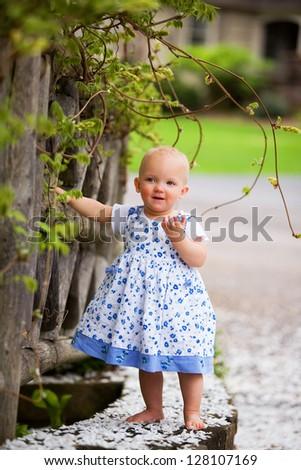 Adorable biracial baby girl playing on a wooden bridge. - stock photo