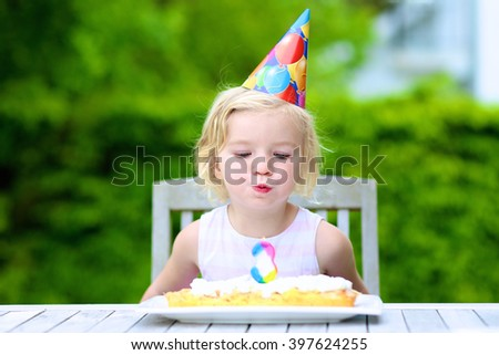 Adorable birthday girl making wish blowing candles on the cake. 3 years old toddler kid celebrating and enjoying party outdoors on summer day. - stock photo