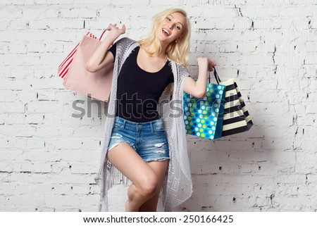 Adorable blond girl against the wall with shopping bags with new purchases laughing out loud wearing summer clothes. - stock photo