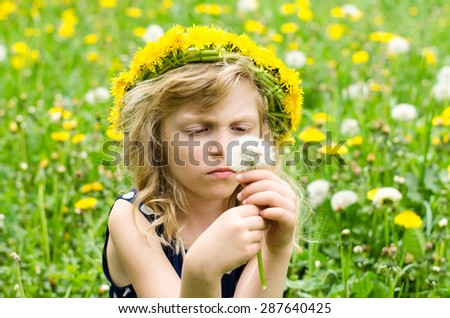 adorable blond girl sitting among white flowers in green woods