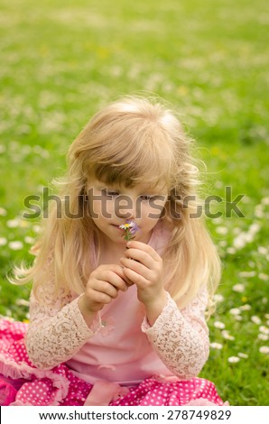adorable blond girl sitting in green meadow and smelling flower