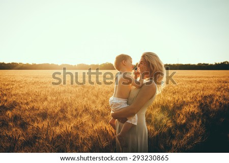 Adorable blond kid boy and his mother having fun on yellow hay field in summer. Happy family of two enjoying nature and togetherness. Boy riding on mum. - stock photo