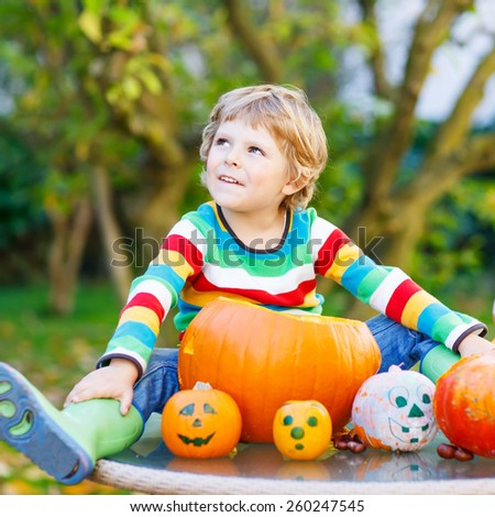 Adorable blond kid boy sitting with traditional jack-o-lantern for halloween in autumn garden, outdoors. Child having fun on sunny warm october day. Creative and active leisure - stock photo