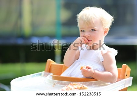 Adorable blond little baby girl in beautiful white dress sitting outdoors in feeding chair eating delicious pizza - stock photo