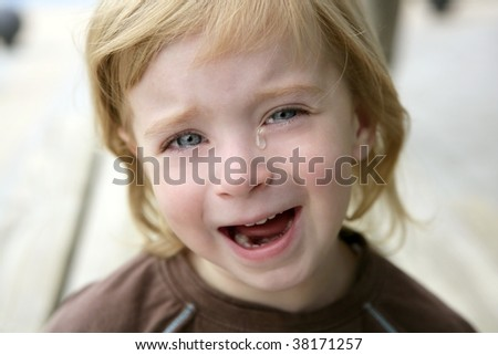 Adorable blond little girl crying closeup portrait