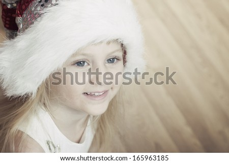 Adorable blond little girl with blue eyes and a furry santa hat. Space for text - stock photo