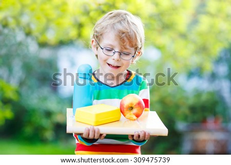 Adorable blond little kid boy with books, apple and drink bottle on his first day to elementary school or nursery. Outdoors.  Back to school, kids, lifestyle concept - stock photo
