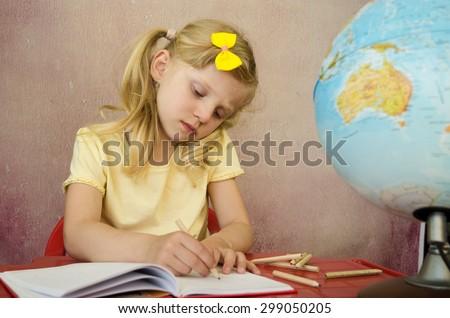 adorable blond schoolgirl doing homework - stock photo