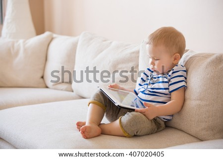 Adorable blond toddler boy laying on the sofa and playing with tablet pc at home, indoors. Child with tablet computer. - stock photo