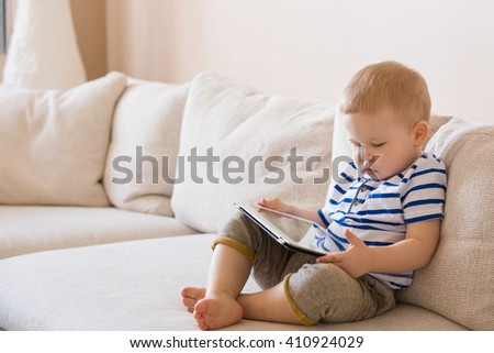 Adorable blond toddler boy laying on the sofa and playing with tablet pc at home, indoors. Child with tablet computer.