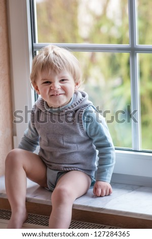 Adorable blond toddler boy looking out of the window