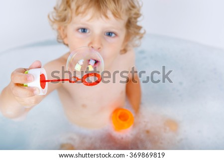 Adorable blond toddler boy playing with soap bubbles by taking bath in bathtub. Selective focus on bubble. Happy kid is surprised. - stock photo