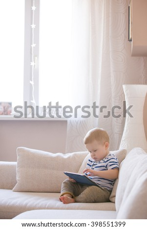 Adorable blond toddler boy sitting on the sofa and playing with tablet pc at home, indoors. Child with tablet computer. White cozy interior. - stock photo
