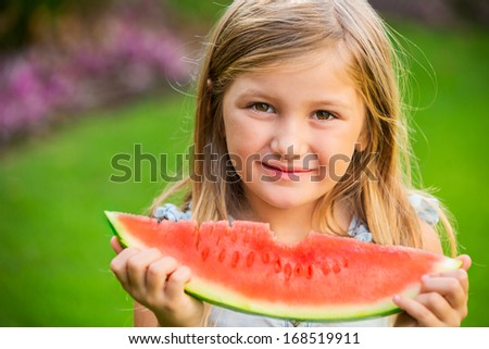Adorable blonde girl eats a slice of watermelon outdoors - stock photo