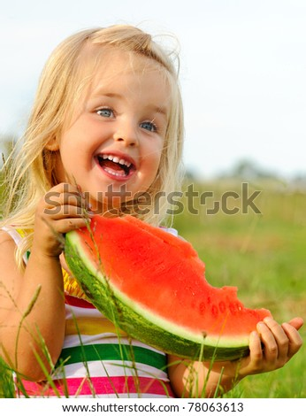Adorable blonde girl eats a slice of watermelon outdoors