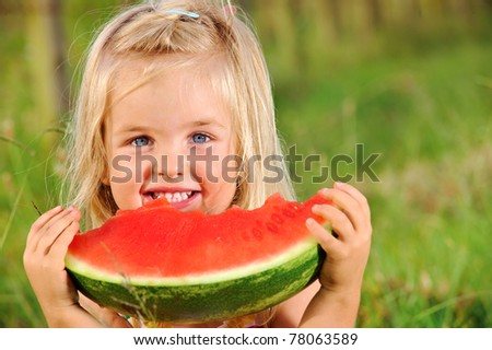Adorable blonde girl eats a watermelon outdoors - stock photo