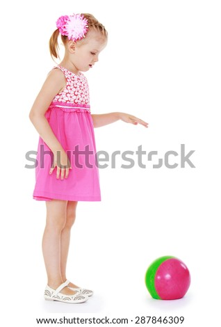 Adorable blonde girl in short summer dress playing ball while standing on the beach-isolated on white background