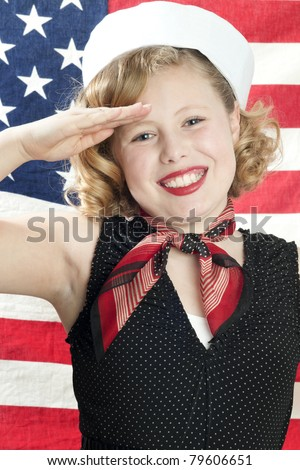 Adorable blonde girl model saluting in front of American flag