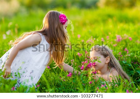 Adorable blonde girls playing on the meadow with pink flowers
