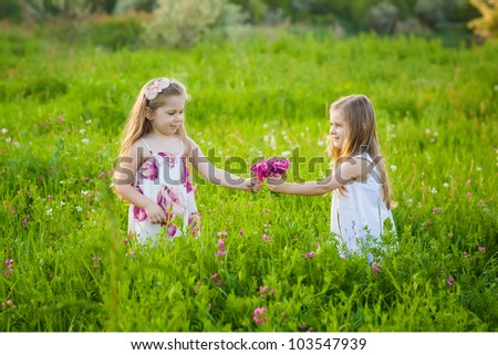 Adorable blonde girls playing on the meadow with pink flowers - stock photo