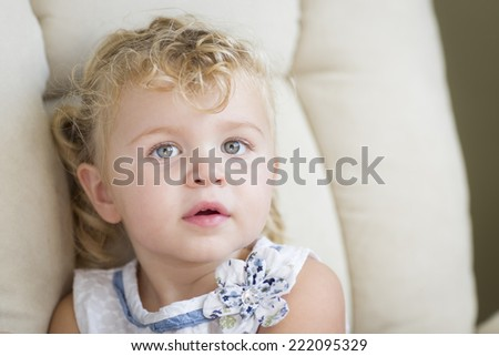 Adorable Blonde Haired and Blue Eyed Little Girl Sitting in Chair. - stock photo