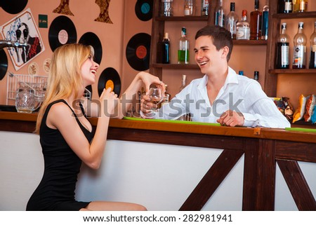 adorable blonde in a black dress flirting with barman. horizontal photo - stock photo