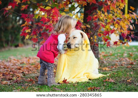 Adorable blonde little girl kissing her dog, a yellow labrador wrapped in a cozy warm blanket in a park with autumn leaves in the background