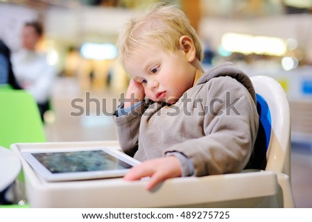 Adorable blonde toddler boy playing with a digital tablet indoors