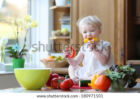 Adorable blonde toddler girl in beautiful white dress eating tasty paprika preparing healthy vegetables salad sitting on the table in sunny kitchen with big garden view window