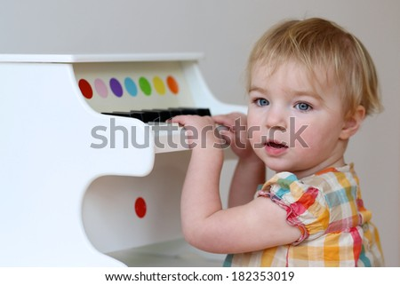 Adorable blonde toddler girl learning to play on piano toy indoors - stock photo