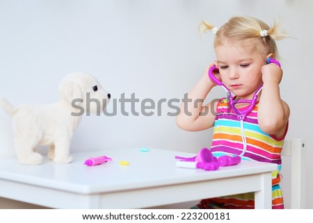 Adorable blonde toddler girl playing doctor role game putting on stethoscope in order to examinate her puppy sitting at small white table in playroom at home, school or kindergarten - stock photo