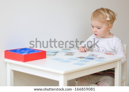 Adorable blonde toddler girl playing memory game sitting at little white table indoors at home or kindergarten - stock photo